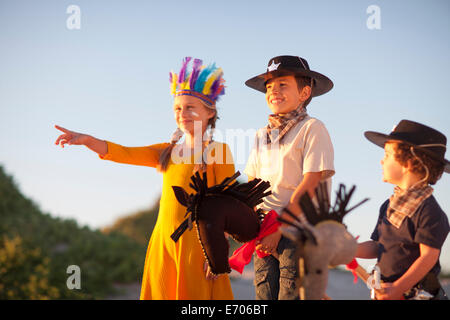 Three children dressed as native american and cowboys pointing from sand dunes