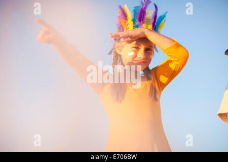 Girl dressed as native american in feather headdress with hand shading eyes and pointing - Stock Photo