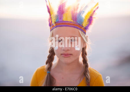 Portrait of girl dressed as native american with feather headdress - Stock Photo