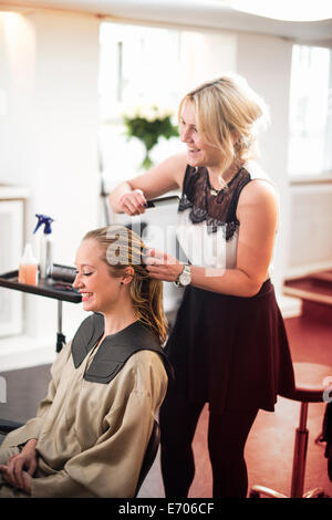 Hairdresser combing customer's hair - Stock Photo