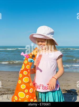 Girl holding up inflatable giraffe, Caleri Beach, Veneto, Italy - Stock Photo