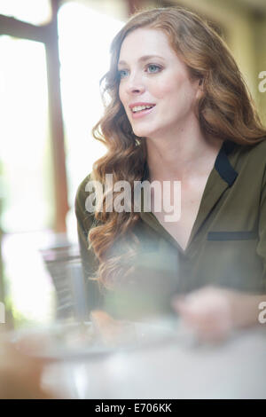 Attractive young woman sitting at restaurant table - Stock Photo