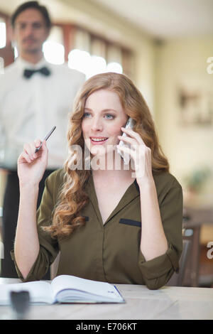 Young businesswoman chatting on smartphone in restaurant - Stock Photo