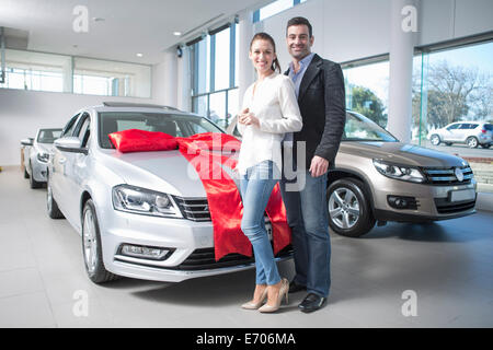 Portrait of mid adult couple and new car with red bow in car dealership - Stock Photo