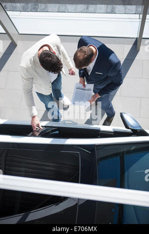 Overhead view of salesman and customer looking at new car in car dealership - Stock Photo