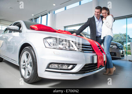 Man looking at new car with red bow with girlfriend in car dealership - Stock Photo