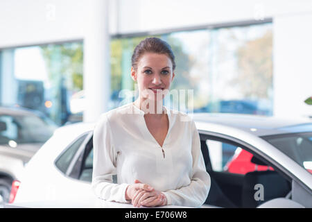 Portrait of smiling saleswoman in car dealership - Stock Photo