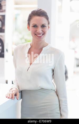Portrait of saleswoman in car dealership - Stock Photo