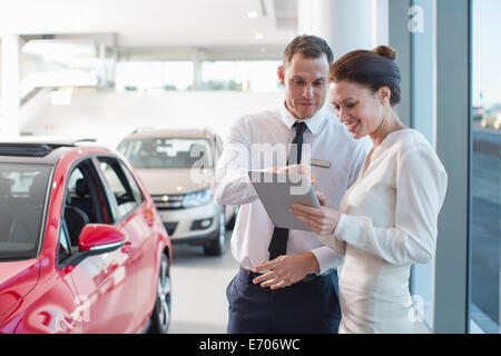Salesman and female customer using digital tablet in car dealership - Stock Photo