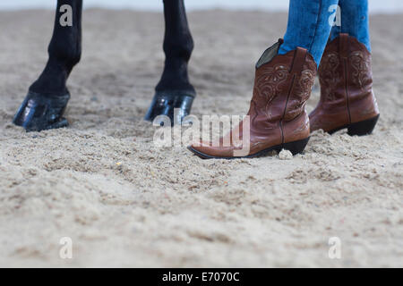 Cropped shot of horse hooves and young woman in cowboy boots - Stock Photo