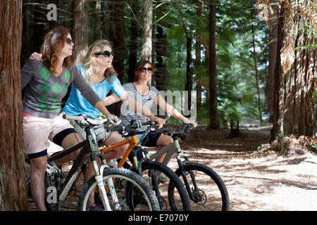 Portrait of three women mountain bikers in forest - Stock Photo