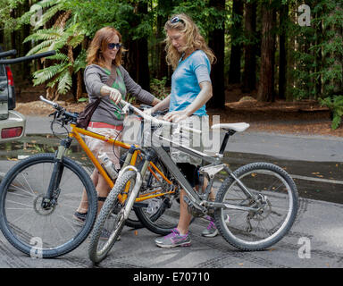 Two women mountain bikers preparing to cycle in forest - Stock Photo