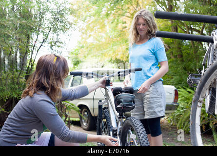 Two women mountain bikers checking cycles in forest - Stock Photo