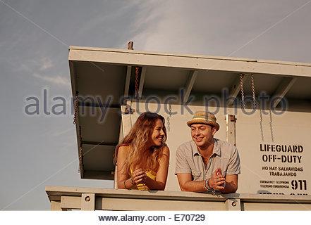 Young couple chatting on lifeguard hut, Santa Monica, California, USA - Stock Photo