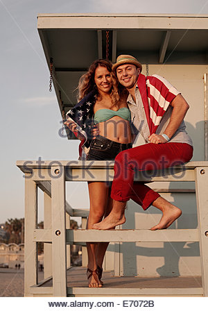 Portrait of young couple wrapped in american flag on lifeguard hut, Santa Monica, California, USA - Stock Photo