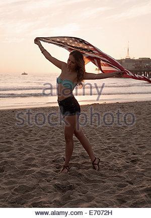 Young woman holding up american flag on beach, Santa Monica, California, USA - Stock Photo