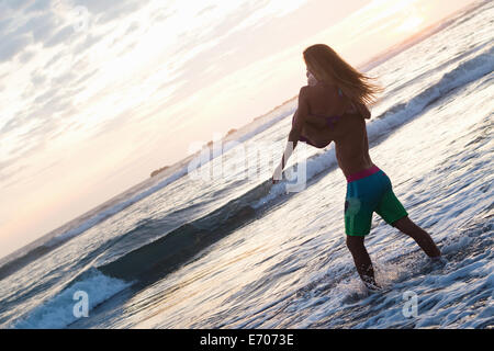 Romantic young man carrying girlfriend in arms on beach, Nosara, Guanacaste, Costa Rica - Stock Photo