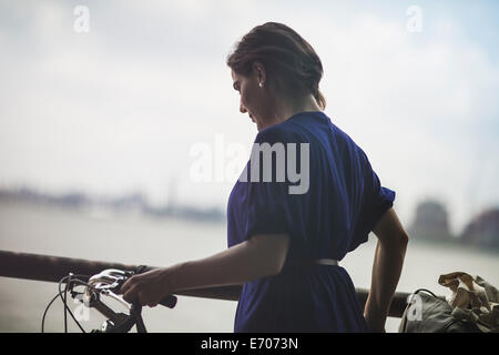 Mid adult woman cyclist pushing bicycle on riverside, New York City, USA - Stock Photo