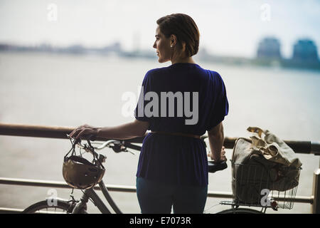 Mid adult woman cyclist with bicycle on riverside, New York City, USA - Stock Photo