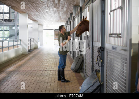 Male stablehand petting horse in stables - Stock Photo