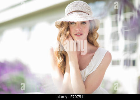 Portrait of beautiful young woman in garden - Stock Photo