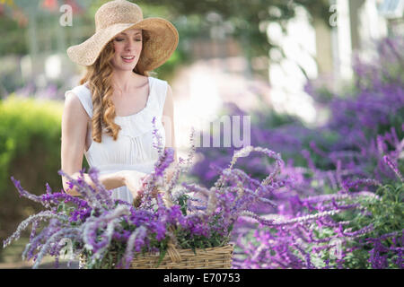 Beautiful young woman in garden looking at purple flowers - Stock Photo