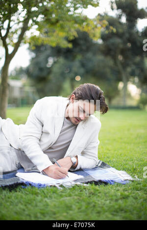 Businessman reclining on picnic blanket writing notes in park - Stock Photo