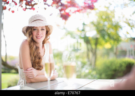 Portrait of beautiful young woman at table in garden restaurant - Stock Photo