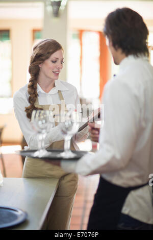 Waiter and waitress carrying trays of wine glasses in restaurant - Stock Photo