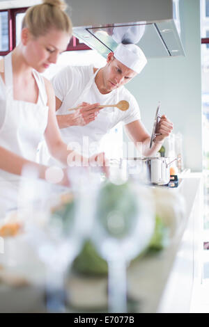 Male and female chefs cooking on hob in commercial kitchen - Stock Photo