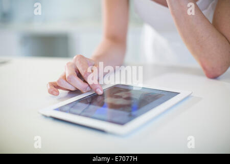 Close up of young womans hand using digital tablet touchscreen on kitchen counter - Stock Photo