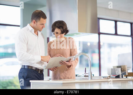 Female customer and salesman looking at brochure in kitchen showroom - Stock Photo