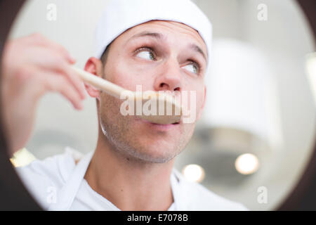 Male chef tasting food from saucepan in commercial kitchen - Stock Photo