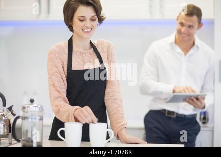 Couple taking a coffee break in kitchen - Stock Photo
