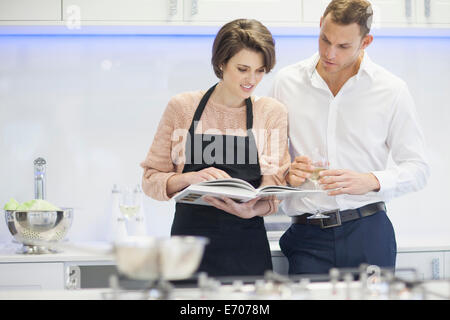 Couple looking at cook book and drinking glass of white wine in kitchen - Stock Photo