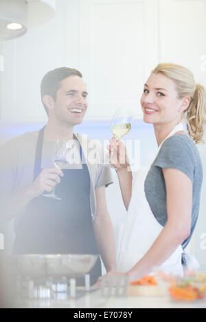 Couple preparing food and drinking glass of white wine in kitchen - Stock Photo