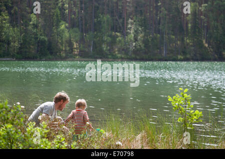 Father and son looking down into lake, Somerniemi, Finland - Stock Photo