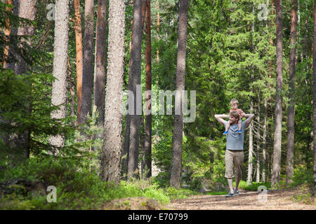 Father shoulder carrying toddler son through forest, Somerniemi, Finland - Stock Photo
