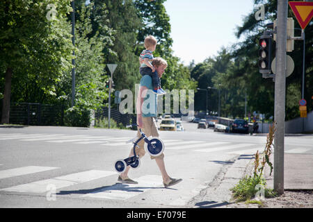 Father shoulder carrying toddler son over pedestrian crossing - Stock Photo