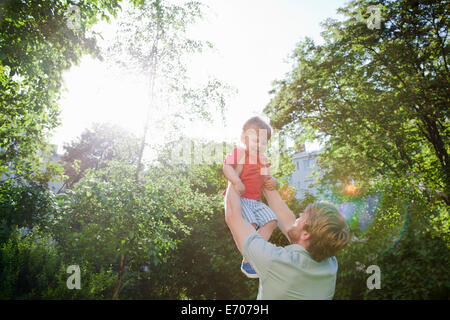 Father holding up toddler son in park - Stock Photo