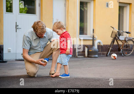Father giving toddler son a hand to put on trainer in garden - Stock Photo
