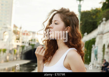 Profile portrait of sullen young woman in city - Stock Photo