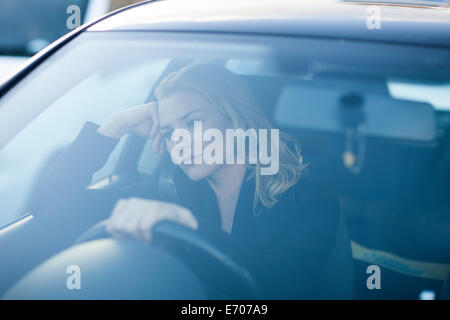 Bored businesswoman staring whilst driving in city traffic jam - Stock Photo