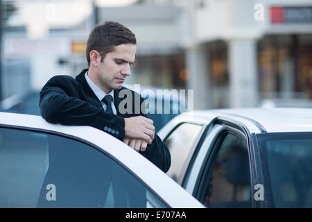 Mid adult businessman looking at watch in city traffic jam - Stock Photo