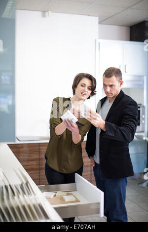 Mid adult couple comparing ceramic tiles in kitchen showroom - Stock Photo
