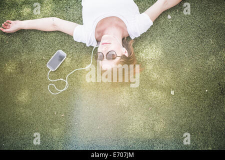 Overhead view of mid adult woman listening to earphones in park - Stock Photo