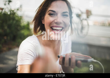 Portrait of laughing mid adult woman holding up earphone - Stock Photo