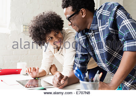 Young couple working on digital tablet - Stock Photo