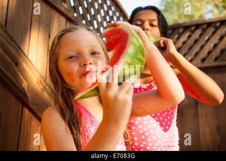 Two girls eating slices of watermelon in garden - Stock Photo
