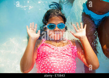 Girl in swimming goggles underwater in garden paddling pool - Stock Photo